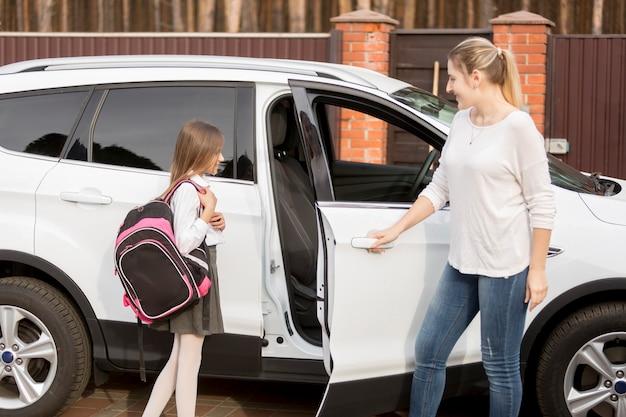 Junge mutter, die tochter nach dem schulunterricht mit dem auto nach hause bringt