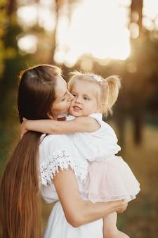 Junge mutter, die um ihrem kleinen baby sich kümmert. mutter und tochter im freien. liebevolle familie. muttertag-konzept