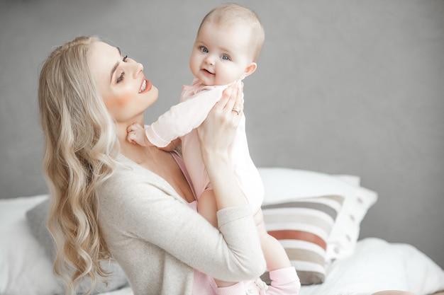 Junge mutter, die um ihrem kleinen baby sich kümmert. schöne mutter und ihre tochter drinnen im schlafzimmer. liebevolle familie. attraktive mutter, die ihr kind hält.