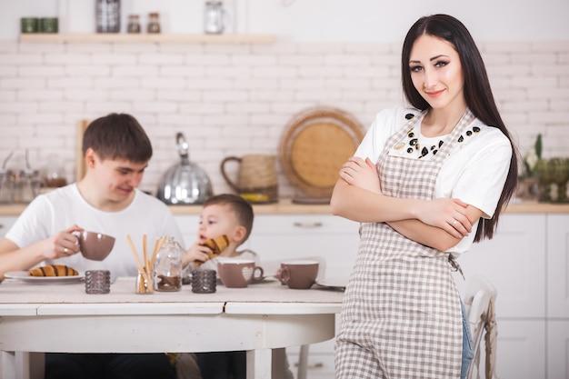 Junge mutter, die vor ihrer familie auf der küche steht. glückliche familie, die zu abend isst oder frühstückt. frau, die abendessen für ihren ehemann und kleines baby macht.
