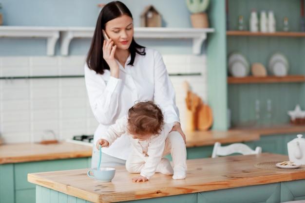 Junge mutter, die zu hause in der küche mit einem baby in ihren armen am telefon spricht