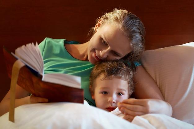 Junge mutter, die zu ihrem kind im bett liest