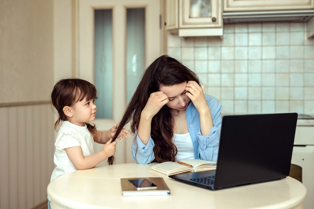 Junge mutter erlebt stress durch freiberufliche arbeit im home office. sie arbeitet an einem laptop in der küche, eine kleine tochter hat spaß und zieht ihre haare von der arbeit ab.