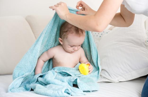 Junge mutter fand ihr baby unter einem blauen handtuch beim spielen mit gelber gummiente