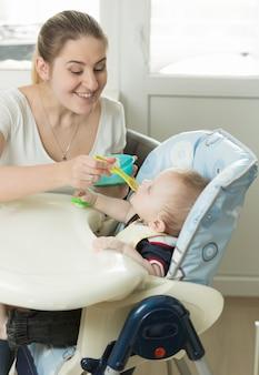 Junge mutter füttert baby im hochstuhl