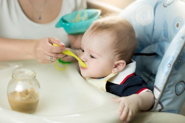 Junge mutter füttert ihr baby im hochstuhl