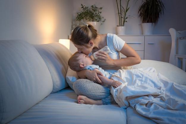 Junge mutter füttert ihr baby nachts aus der flasche im bett