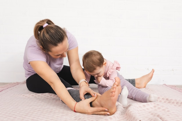 Junge mutter gymnastik zu hause ein jahr altes kind verwenden smartphone freizeit familienkonzept