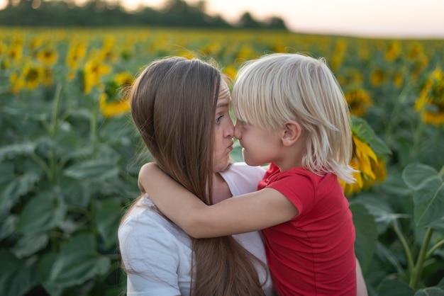Junge mutter hält ihren sohn in ihren armen auf sonnenblumenfeldhintergrund. mutter und sohn reiben sich lustig die nase