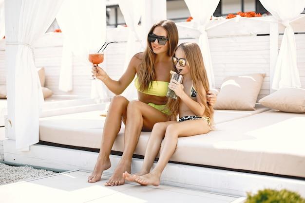 Junge mutter hat urlaub mit ihrem kind. beide tragen badeanzüge und sitzen auf einer weichen sonnenliege mit cocktail. sommerferienkonzept, familienbeziehung. europäisch.