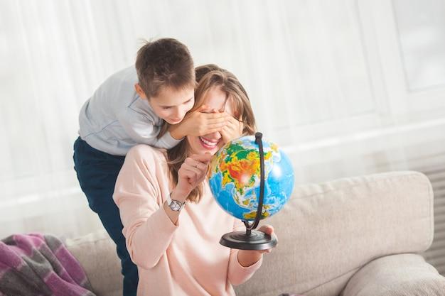Junge mutter hilft ihrem sohn, hausaufgaben zu machen. familie wählt, wohin sie im urlaub reisen möchten. mutter und ihr kind halten einen globus