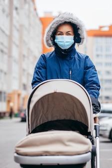 Junge mutter in der chirurgischen maske und in den handschuhen, die mit baby im freien in europa gehen