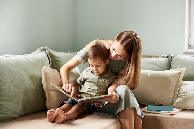 Junge mutter, las ihrem kind ein buch vor, junge im wohnzimmer ihres hauses, sonnenstrahlen gehen durch das fenster
