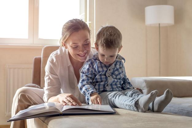 Junge mutter liest ein buch für ihren kleinen jungen mit blauem hemd