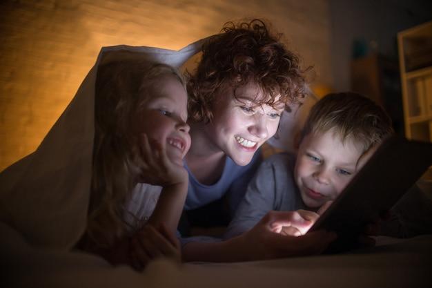Junge mutter liest geschichten mit zwei kindern