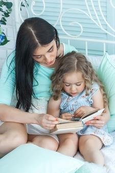 Junge mutter liest ihrer kleinen schläfrigen tochter ein märchen vor