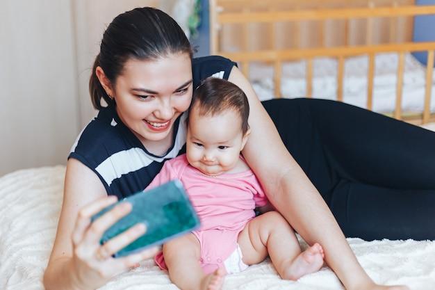Junge mutter macht selfie mit ihrem entzückenden kleinen baby