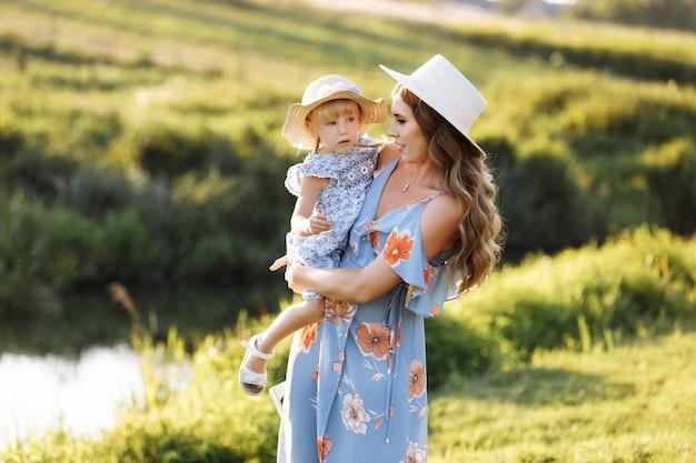 Junge mutter mit baby nahe flusshintergrund.