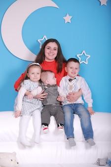 Junge mutter mit baby und zwei kleinen kindern auf einem weißen sofa. blaue wand mit einem weißen mond und sternen an einer wand.