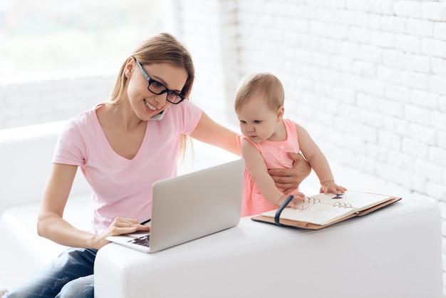 Junge mutter mit dem baby, das laptop bearbeitet und verwendet.