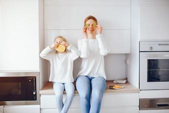 Junge Mutter mit dem hellen Haar in der weißen Spitze und in der Blue Jeans-Hose, die zu Hause sitzt