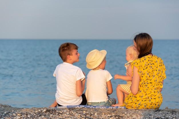 Junge mutter mit drei kindern ruht am meer. rückansicht. familienurlaub am meer.