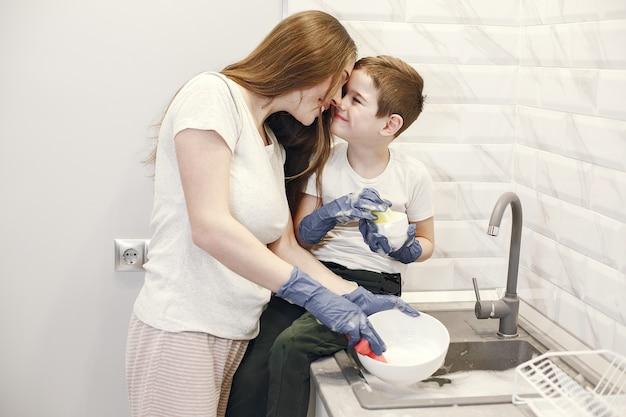 Junge mutter mit einem jungen, der geschirr in der küche spült.
