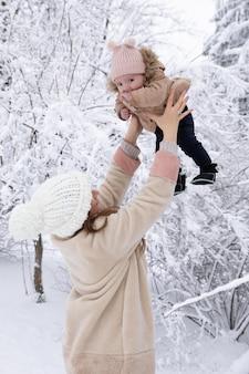 Junge mutter mit einem kleinen kind, das im schnee spielt