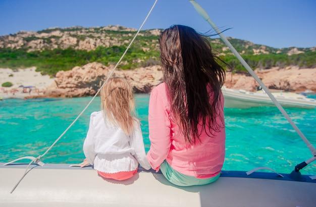 Junge mutter mit ihrem entzückenden kleinen mädchen, das auf einem großen boot stillsteht