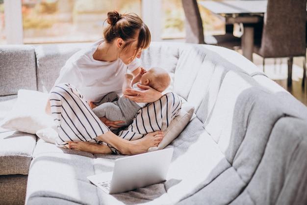 Junge mutter mit ihrem kind, das zu hause an einem computer arbeitet