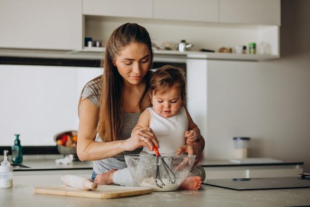 Junge mutter mit ihrem kleinen sohn, der in der küche kocht