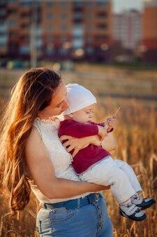 Junge mutter mit ihrem netten kind, den sonnigen tag über sommerfeld genießend.
