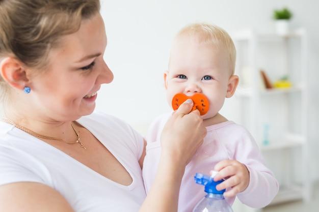 Junge mutter mit ihrem niedlichen kleinen baby zu hause nahaufnahme