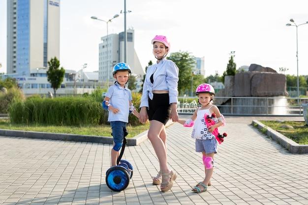 Junge mutter mit ihren kindern sohn und tochter fahren ein skateboard und einen kreiselroller im park.