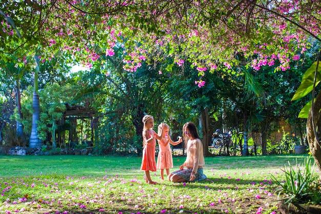 Junge mutter mit ihren kleinen töchtern, die im üppigen garten sitzen und sommerruhe genießen
