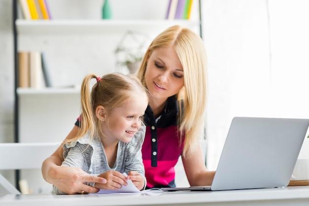 Junge mutter mit ihrer glücklichen tochter, die zu hause laptop verwendet