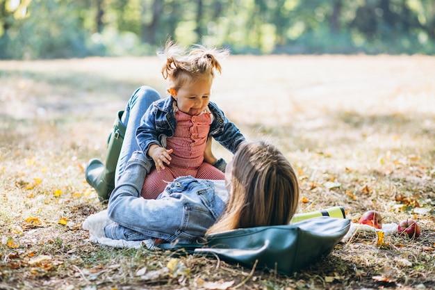 Junge mutter mit ihrer kleinen tochter in einem herbstpark, der picknick hat