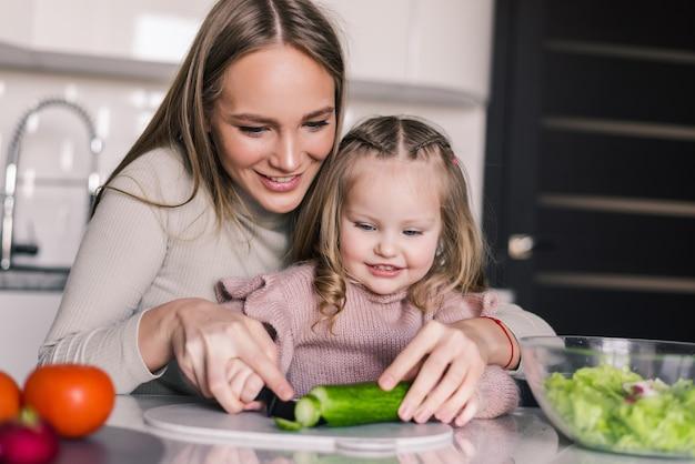 Junge mutter mit ihrer tochter bereitet mittagessen in der küche vor und genießt zusammen