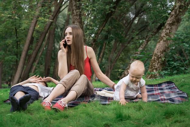 Junge mutter mit kind, das auf picknickdecke sitzt und am telefon spricht. geschäftsfrau mit baby