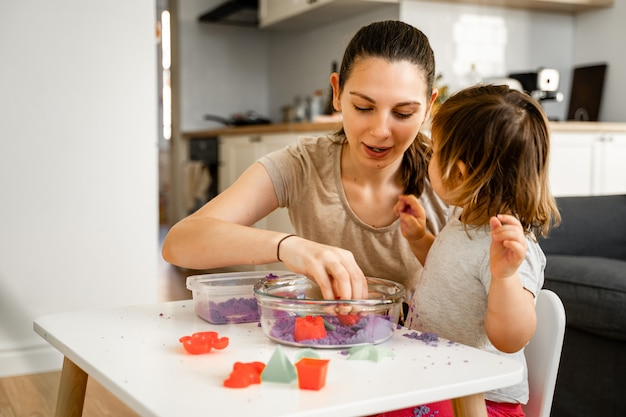 Junge mutter mit kind, das kinetischen sand spielt. fröhliche zeit miteinander. kreativitätsentwicklung