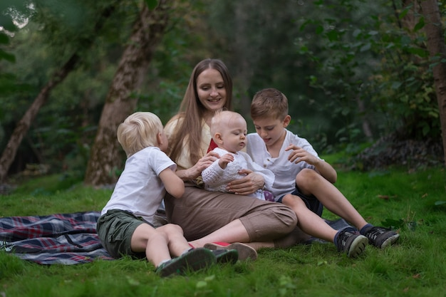 Junge mutter mit kleinen kindern, die im sommer picknick haben. glückliche familie, die auf wiese sitzt