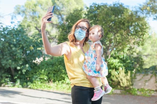 Junge mutter mit schutzmaske mit ihrem baby in den armen mit handy im freien