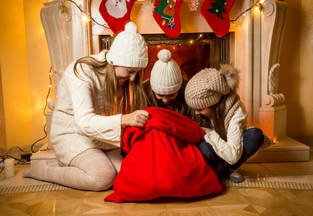 Junge mutter mit zwei töchtern, die in die rote tasche des weihnachtsmanns schauen