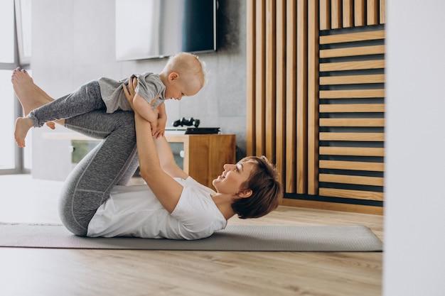 Junge mutter praktiziert yoga mit ihrem kleinkindsohn auf matte