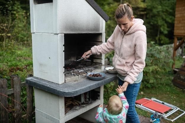 Junge mutter röstet draußen im hinterhof kastanien und übergibt eine davon an ihre kleinkindtochter.