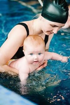 Junge mutter, schwimmlehrerin und glückliches kleines mädchen im planschbecken. bringt dem kleinkind das schwimmen bei. genießen sie den ersten tag im wasser schwimmen. mutter hält handkind, das sich auf das tauchen vorbereitet. übungen machen