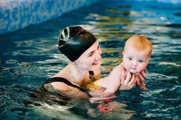 Junge mutter, schwimmlehrerin und glückliches kleines mädchen im pool. bringt dem kleinkind das schwimmen bei. genießen sie den ersten tag im wasser zu schwimmen. mama hält kind, das sich auf das tauchen vorbereitet. übungen machen.