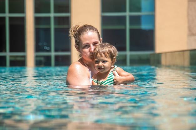 Junge mutter schwimmt mit ihrer kleinen tochter im pool auf dem dach eines hochhauses in einer metropole...