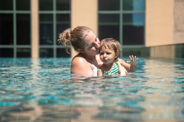 Junge mutter schwimmt und küsst ihre kleine kleinkindtochter im stadtpool ...