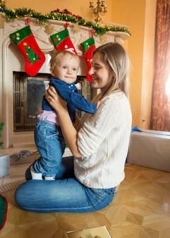 Junge mutter sitzt mit ihrem baby auf dem boden am weihnachtsbaum